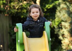 Toddler using slide at safe nursery setting