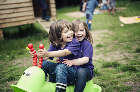 two children play outside in Nursery play area