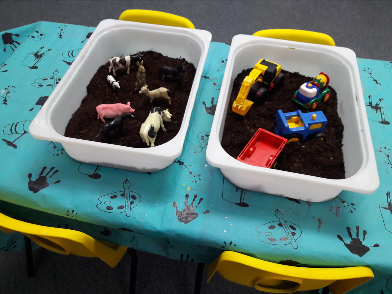 Teachers help young toddlers be creative with mud and farm toys