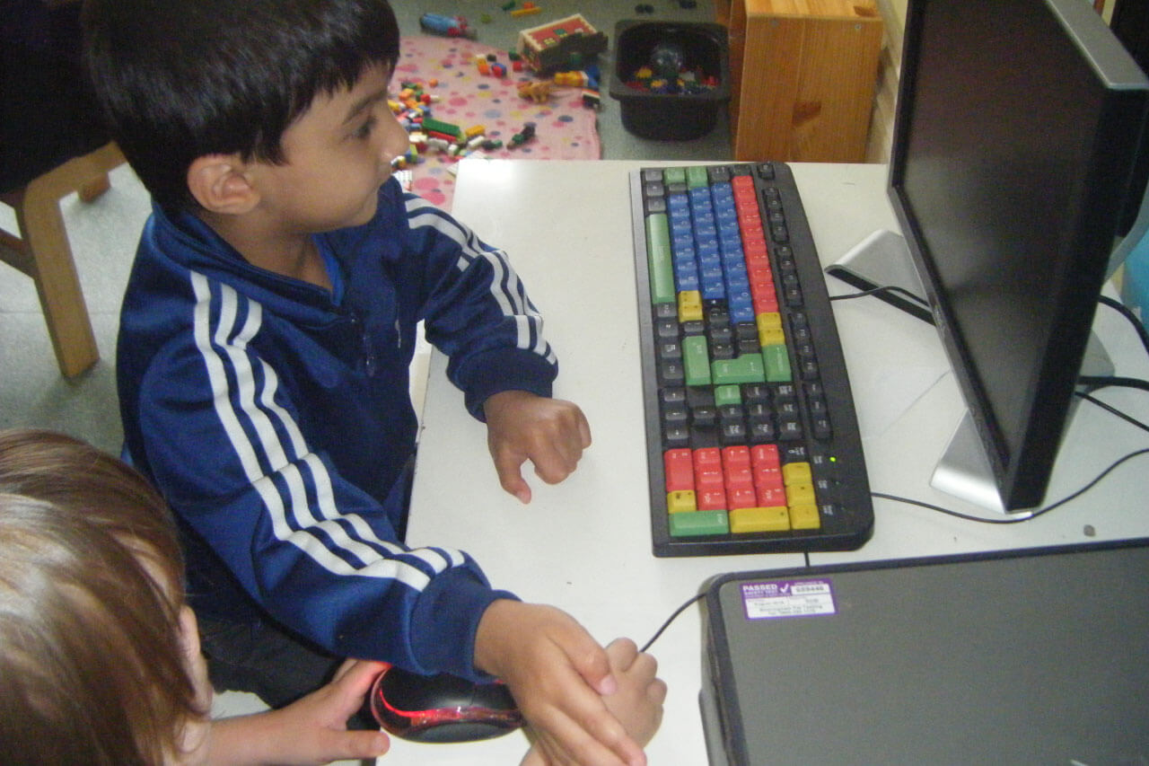 Young child using the nursery school computer to learn