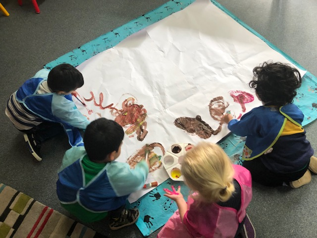 Four children paint together on a large sheet of paper