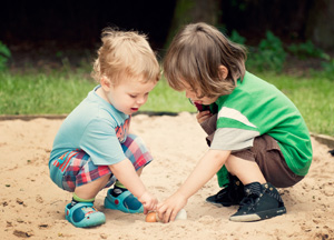 Children in sandpit playing and learning together