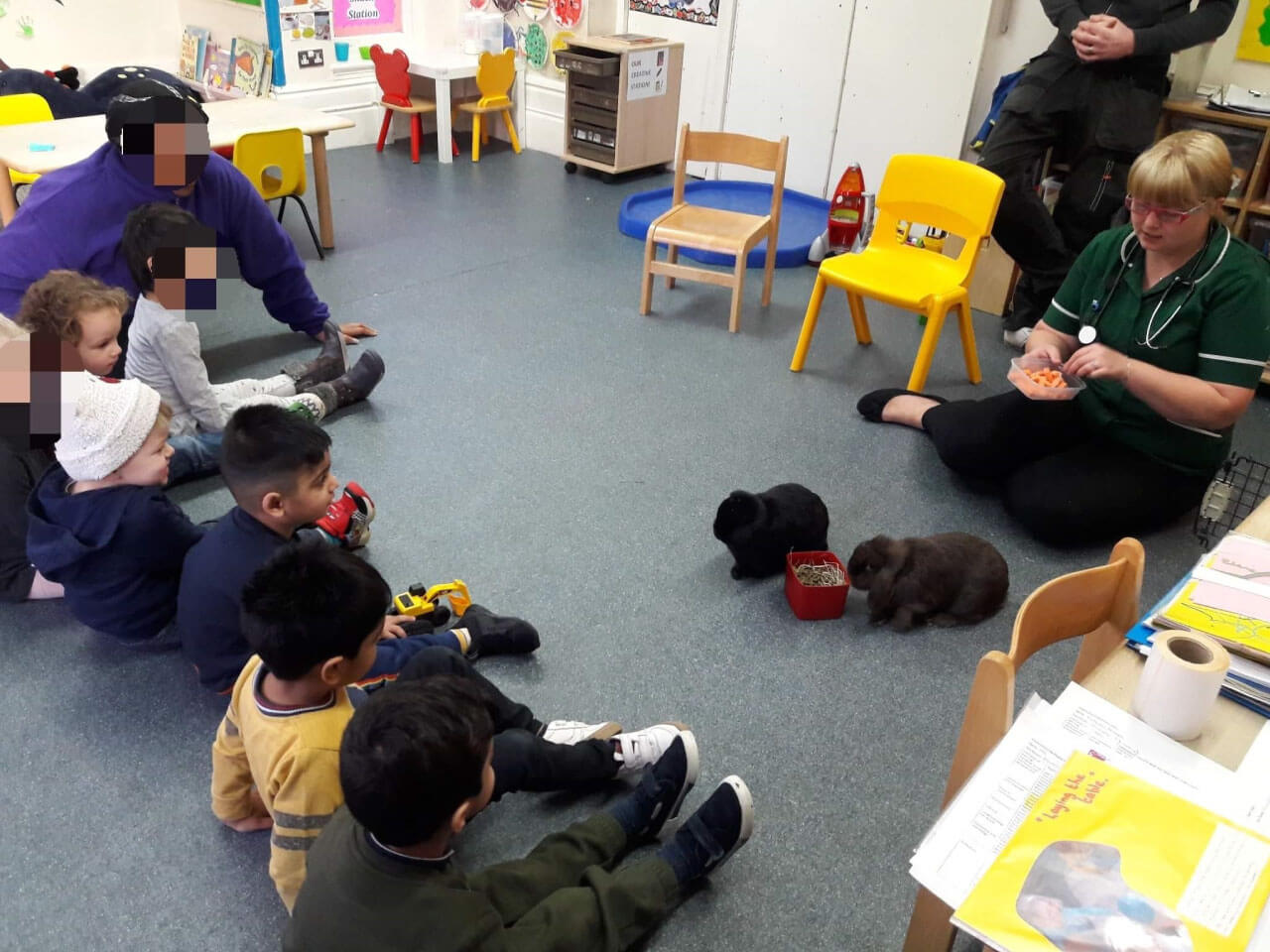 Toddlers having lesson with local vet about rabbits