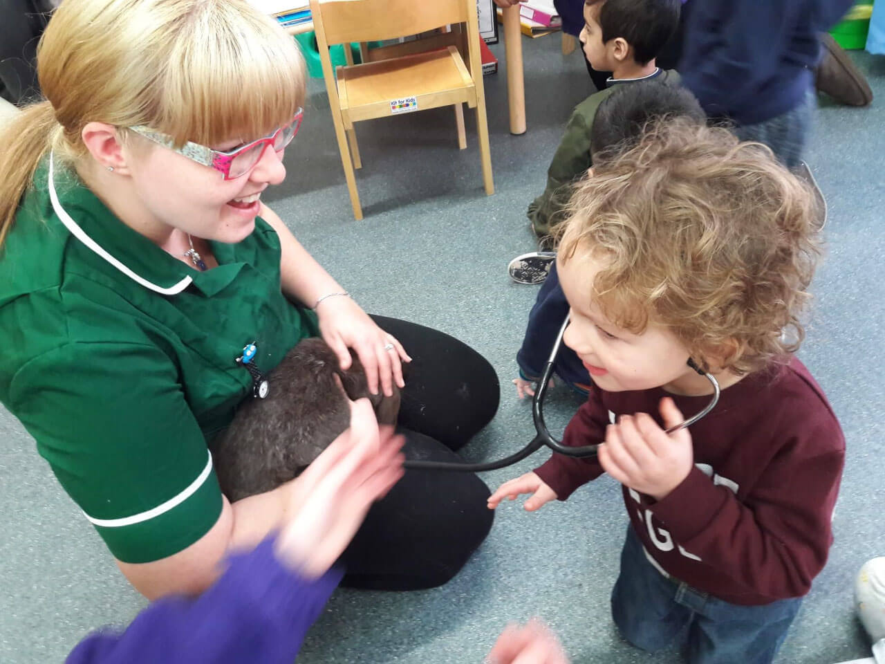 Vet showing toddler how to hear a rabbits heart beat